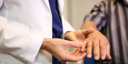 A doctor helps a patient move their hand.