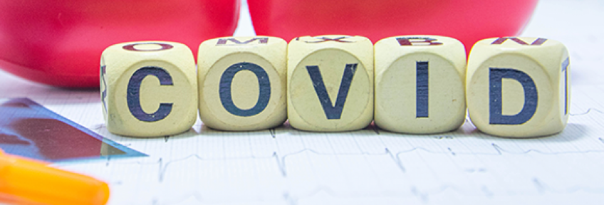 """A set of blocks spell out """"COVID"""" in front of two hearts."""