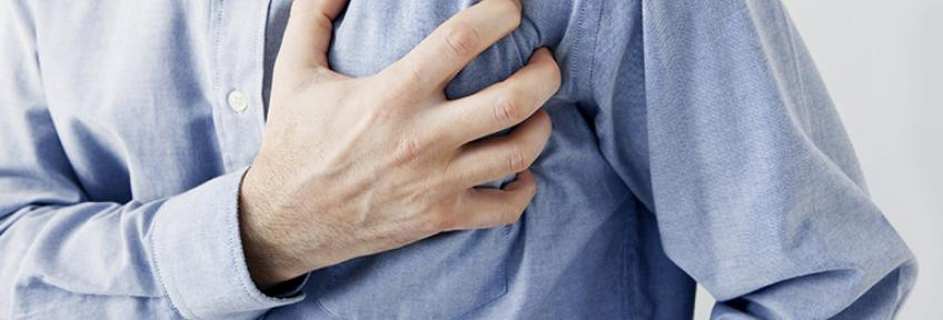 A man clutches his chest and thinks he might be experiencing a heart attack.