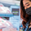 A woman reads the nutrition label on a package of deli meat.